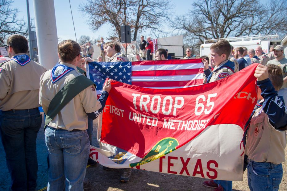 Boy Scouts color guard members in Denton present the U.S. flag and the Troop 65 flag to raise it on the flag pole.