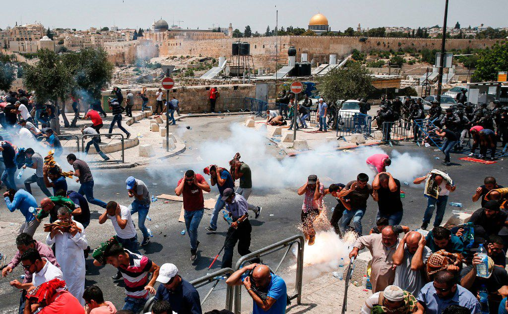 Palestinian worshippers ran for cover from tear gas fired by Israeli forces outside Jerusalem's Old City in front of the Al-Aqsa mosque compound on July 21, after Israeli police barred men under 50 from entering the Old City for Friday Muslim prayers as tensions rose and protests erupted over new security measures at the highly sensitive holy site.  The ban came after Israeli ministers decided not to order the removal of metal detectors erected at entrances to the Al-Aqsa mosque compound, known to Jews as the Temple Mount, following an attack nearby a week ago that killed two policemen.
