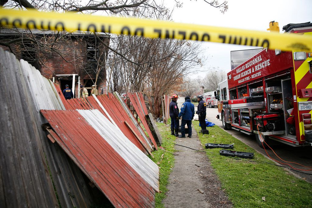 Dallas and Cedar Hill fire-rescue workers reinforce a house that caught fire early Thursday morning. Three people died in the home in the 700 block of Lovern Street in Cedar Hill.