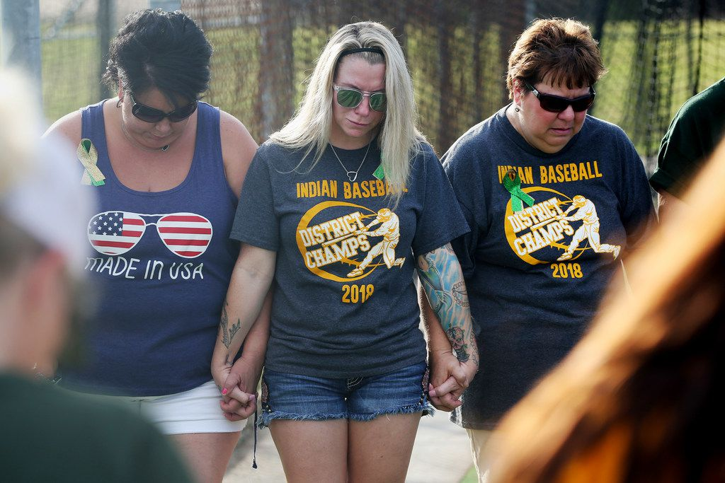 Supporters of Santa Fe baseball player join hands before the second game of the best-of-three series in the Class 5A Region III playoff high school baseball game between Santa Fe and Kingwood Park at Jim Kethan Field at Deer Park High School in Deer Park, TX Saturday May 19, 2018. On Friday morning, 10 people were killed and 13 were injured after a shooting at Santa Fe High School. The game was postponed to Saturday after it was scheduled for Friday. Dimitrios Pagourtzis was booked into the Galveston County Jail on capital murder charges.