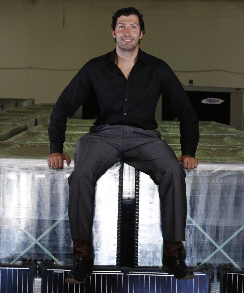 Abe Issa, CEO of Global Efficient Energy, poses with solar panels in the company''s warehouse in Fort Worth.