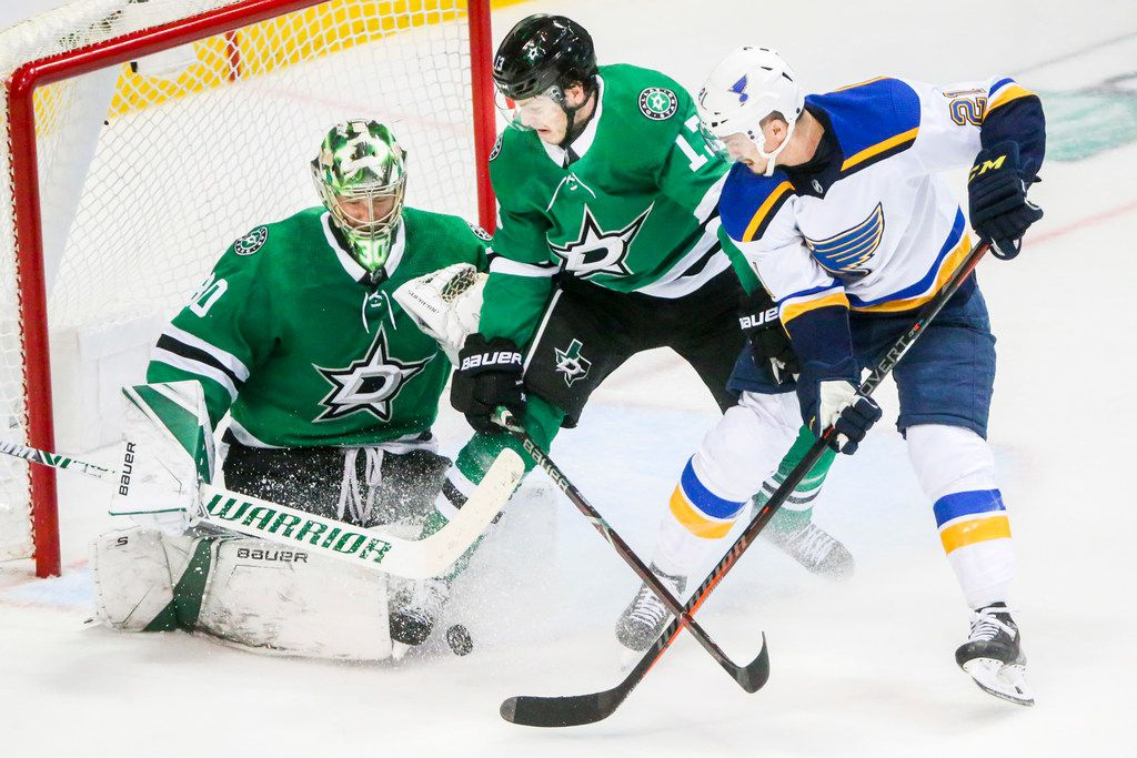 St. Louis Blues center Tyler Bozak (21) takes a shot on goal as Dallas Stars goaltender Ben Bishop (30) and center Mattias Janmark (13) defends during game 3 of an NHL second round playoff series at American Airlines Center in Dallas on Monday, April 29, 2019. (Shaban Athuman/Staff Photographer)