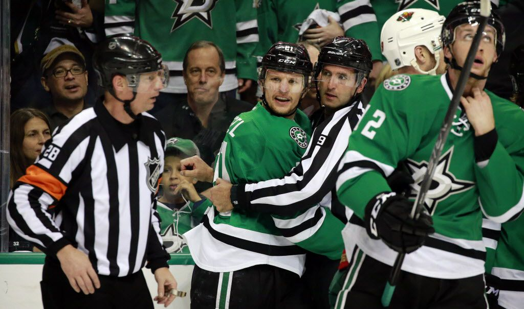 Dallas Stars left wing Antoine Roussel (21) is restrained by referee Dan O'Rourke (9) after getting in a first period fight with the Minnesota Wild during Game 5 of the Western Conference Quarterfinals at the American Airlines Center in Dallas, Friday, April 22, 2016. (Tom Fox/The Dallas Morning News)