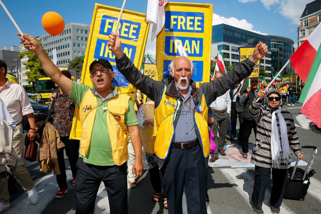 People wave Iranian national flags and hold signs as they take part in a march organized for a free Iran and protesting the Iranian regime on June 15, 2019, in Brussels. This march is the first of a several around the world to protest against the Iranian regime.