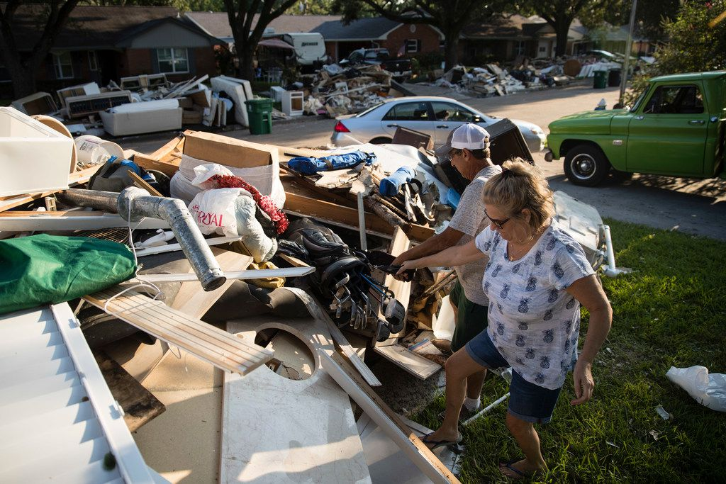 In this Wednesday, Sept. 6, 2017, photo, Blatt helps his neighbor Tamlyn Lima collect golf clubs from debris piled in front of her home in the aftermath of Hurricane Harvey in Houston. Harvey's record-setting rains now have the potential to set records for the amount of debris one storm can produce. (AP Photo/Matt Rourke)