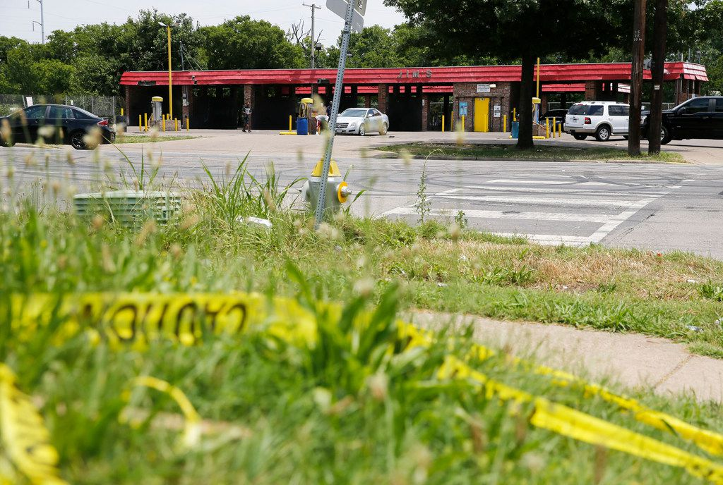 Caution tape on the ground across the street from Jim's Car Wash in Dallas on Monday, June 3, 2019. Four gunshot victims were found at the car wash on Sunday evening. One was killed and four people were injured in the shooting. (Vernon Bryant/The Dallas Morning News)