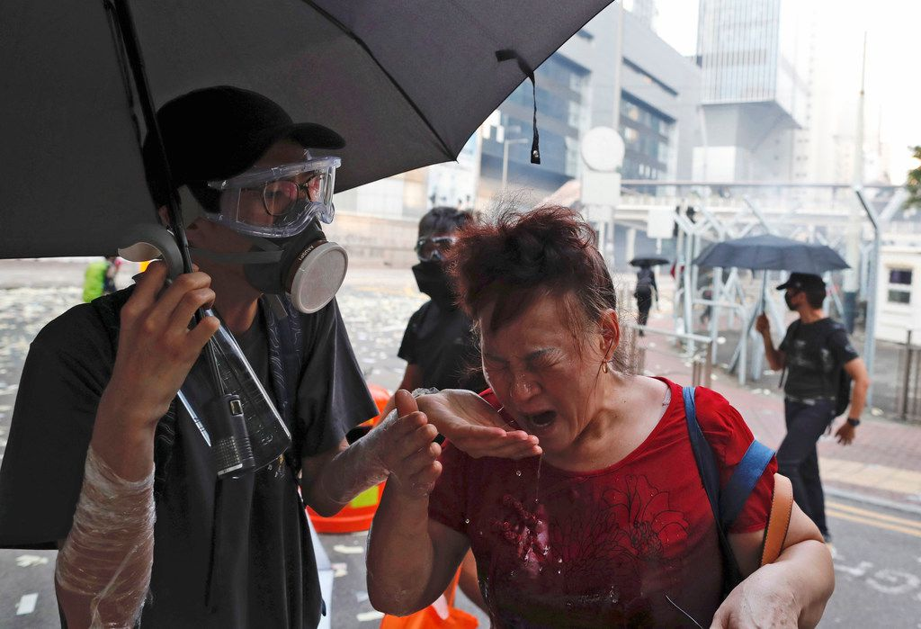 A black-clad protestor splashes water on the face of a woman after police fired tear gas shells in Hong Kong, Tuesday, Oct. 1, 2019. A Hong Kong police official says a pro-democracy protester was shot when an officer opened fire with his revolver during clashes Tuesday. A video of the incident, shot by the City University Student Union and shared on social media, shows a dozen black-clad protesters hurling objects at a group of riot police pursuing them. One officer, who was surrounded, drew his revolver and pointed it at the group. He fired and one protester collapsed on the street while others fled. (AP Photo/Gemunu Amarasinghe)