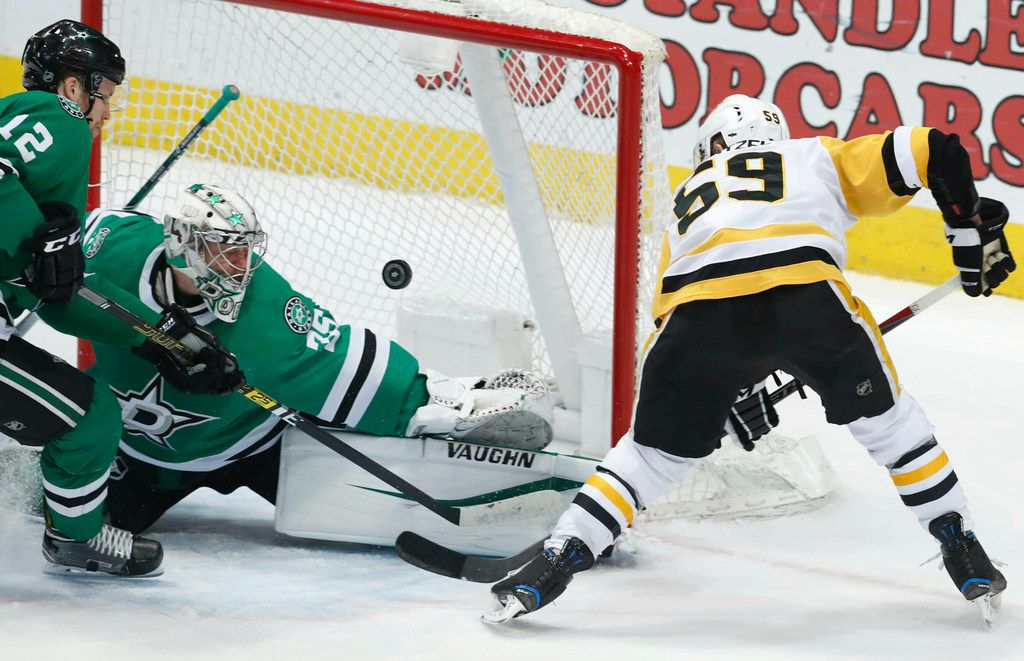 Pittsburgh Penguins left wing Jake Guentzel (59) takes a shot on goal against Dallas Stars goaltender Anton Khudobin (35) and defenseman Taylor Fedun (42) during the first period of an NHL hockey game in Dallas, Saturday, March 23, 2019. (AP Photo/LM Otero)