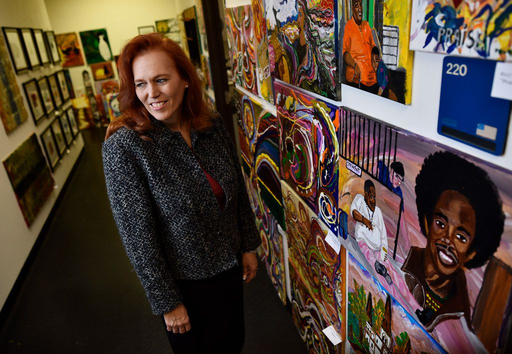 Brenda Snitzer walks the halls at The Stewpot offices that features work from the agency's art program.