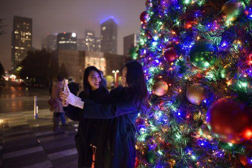 Eunji y Yegi Lee, de Dallas, se hacen un selfie con el árbol navideño en Klyde Warren Park.