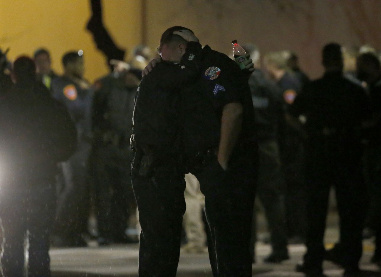 Police officers console each other Tuesday night outside the emergency room at Medical City Denton.
