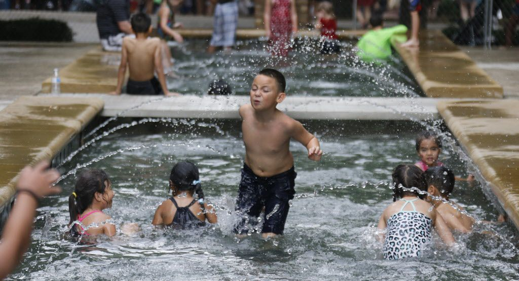Youngsters enjoy the cool water in the fountains at Addison town circle during the City of Addison's Kaboom Town celebration on Friday, July 3, 2015.