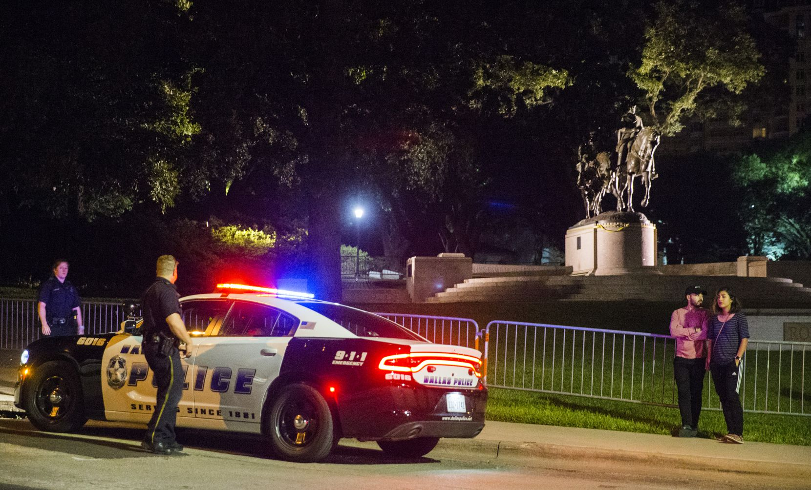 Police officers patrol the area around a statue of Robert E. Lee around 10:30 p.m. on Sept. 6, 2017 at Robert E. Lee Park in the Turtle Creek area of Dallas.