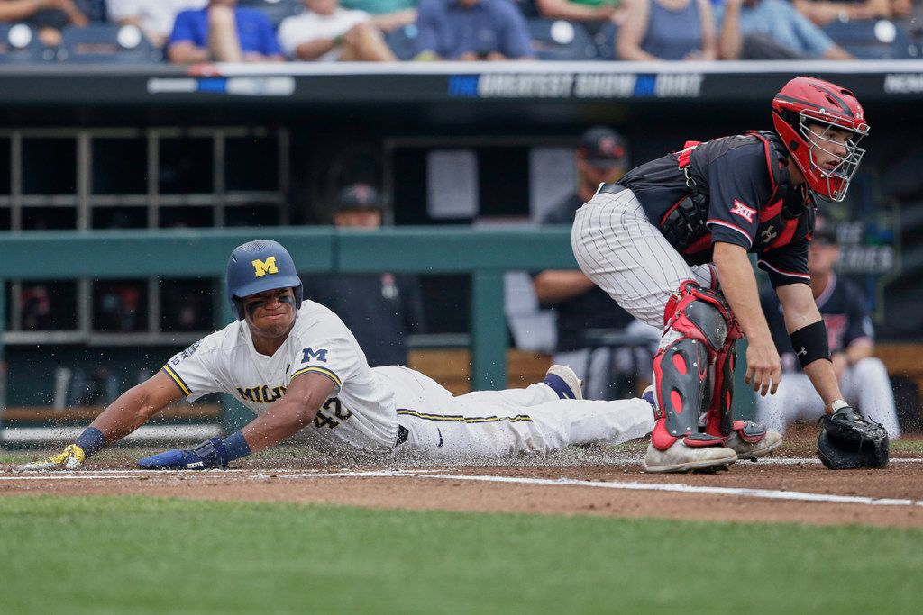 Michigan's Jordan Nwogu (42) scores on a sacrifice fly by Jordan Brewer as Texas Tech catcher Braxton Fulford, right, waits for the throw, in the first inning of an NCAA College World Series baseball game in Omaha, Neb., Saturday, June 15, 2019. (AP Photo/Nati Harnik)