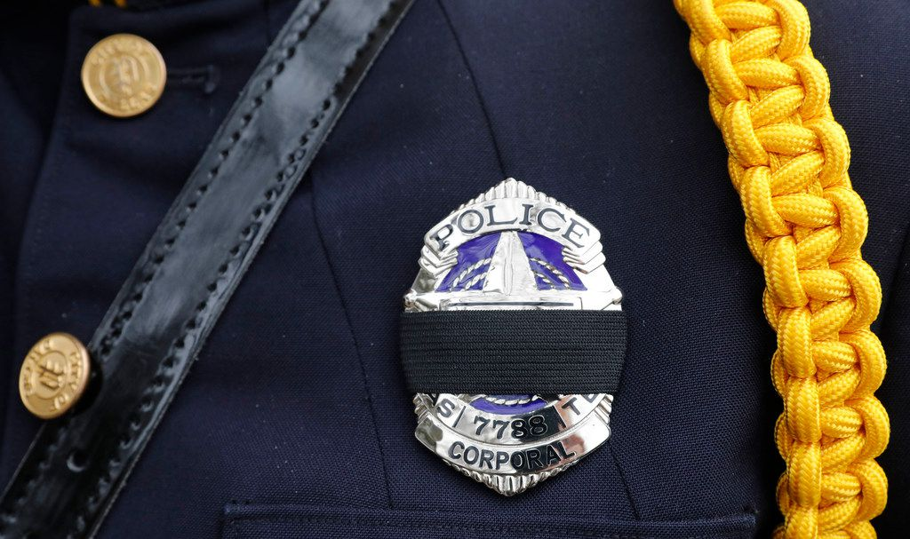 A black mourning band covers the badge of Dallas police office C. Anderson honoring Richardson police officer David Sherrard outside of Watermark Community Church in Dallas, Texas, Tuesday, February 13, 2018.