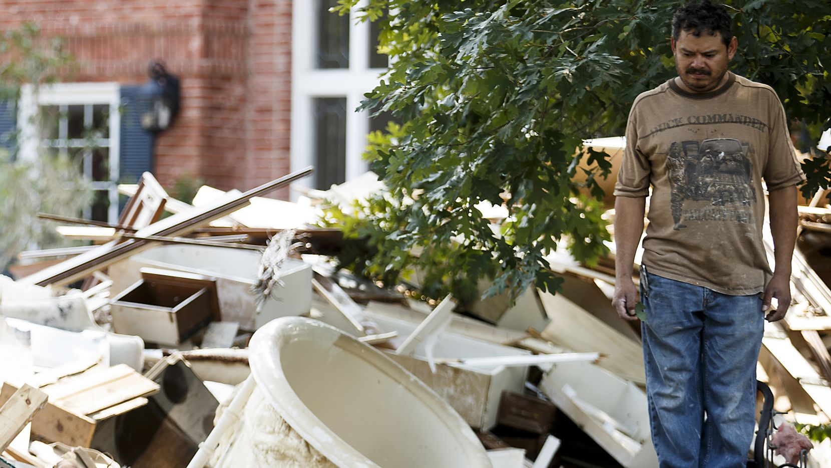 A worker stands amidst a pile of rubble in front of a house damaged by flooding from Hurricane Harvey in Houston.