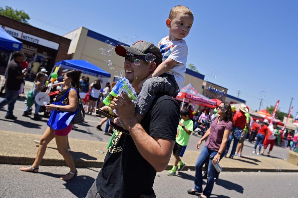 Andrew Rodríguez lleva a su hijo Drew, por la Jefferson Boulevard, Oak Cliff, durante las celebraciones del Cinco de Mayo. BEN TORRES/AL DÍA