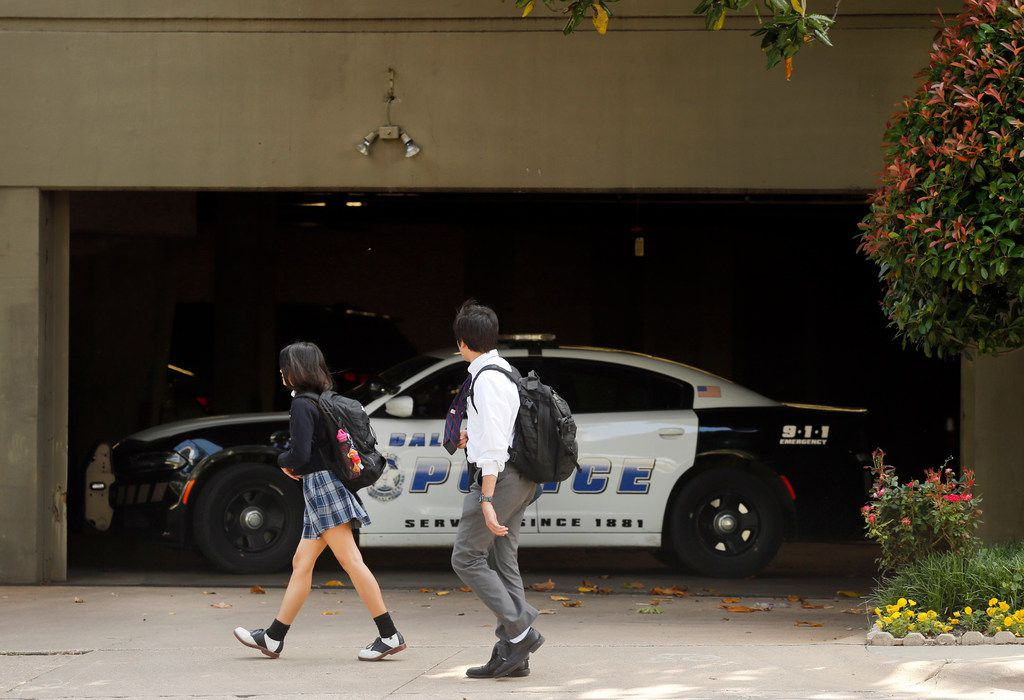 Students walking home from school Wednesday passed by a Dallas police in font of the Catholic Diocese of Dallas parking garage. Dallas police raided several diocese offices on Wednesday.