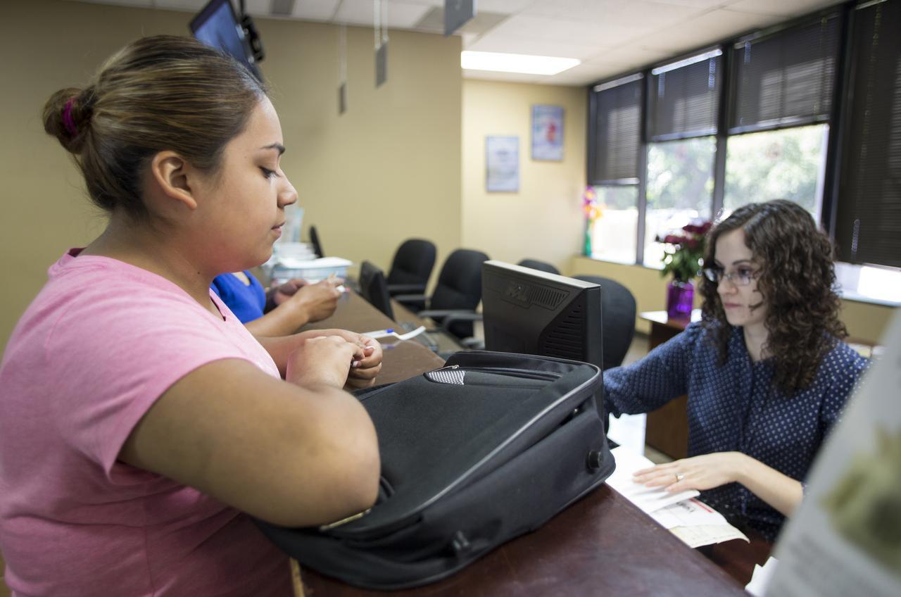 Selma Guerrero (izq.) espera que Esperanza Hernandez procese su trámite para la importación temporal de un vehículo a México, el martes en las oficinas de Banjército en Dallas. (MARÍA OLIVAS/Especial para AL DÍA)