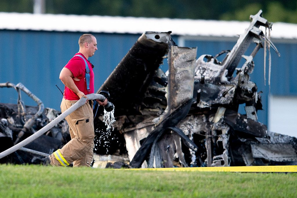 A firefighter carries a hose past wreckage of the plane in which Dale Earnhardt Jr., his wife and daughter were passengers, following a crash near Elizabethton Municipal Airport in Elizabethton, Tenn., Thursday, Aug. 15, 2019. Everyone on board survived the crash. (Calvin Mattheis/Knoxville News Sentinel via AP)