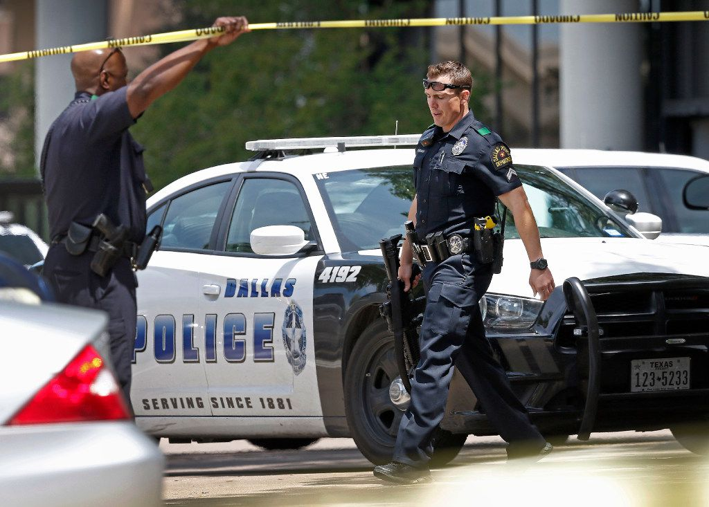 A Dallas Police Department officer (right) with an rifle leaves a shooting scene where police found two people dead at an office building in Lake Highlands near the High Five in Dallas, Monday, April 24, 2017. (Jae S. Lee/The Dallas Morning News)