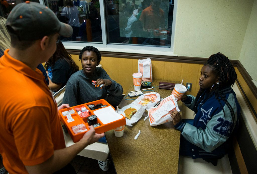 Lone Star High School students Kennedy McGilvery (second from left), 17, and Destiny Licorish, 16, chat with classmate and Whataburger employee Kevin Clark, 16, as they celebrate their district football title at Whataburger in Frisco.
