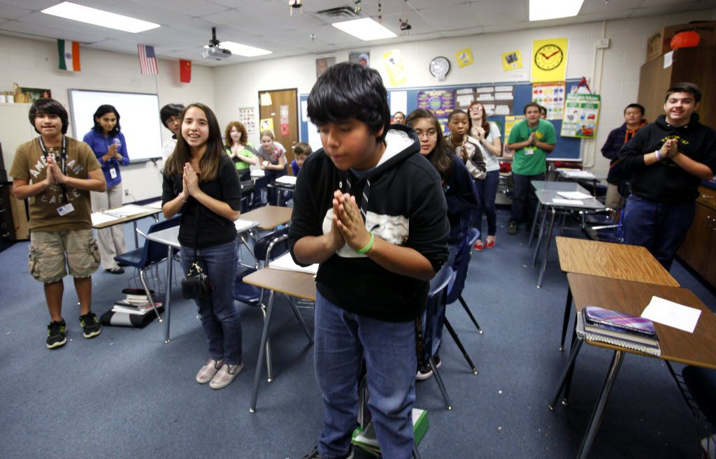 Seventh grade students David Rodriquez, Shazy Rubio and Alfredo Garnica (from left) greet visitors by bowing and saying Namaste in a Hindi class at Central Junior High in Bedford on Friday, December 14, 2012.