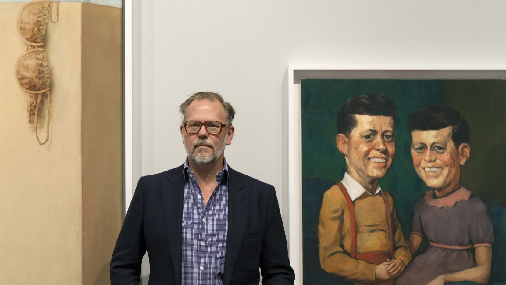 """Artist John Currin, photographed at his exhibition """"My Life as a Man"""" at the Dallas Contemporary. He is flanked by his works """"The Kennedys"""", with two images of John F. Kennedy (right), and a detail of """"The Dream of the Doctor"""" (left)."""