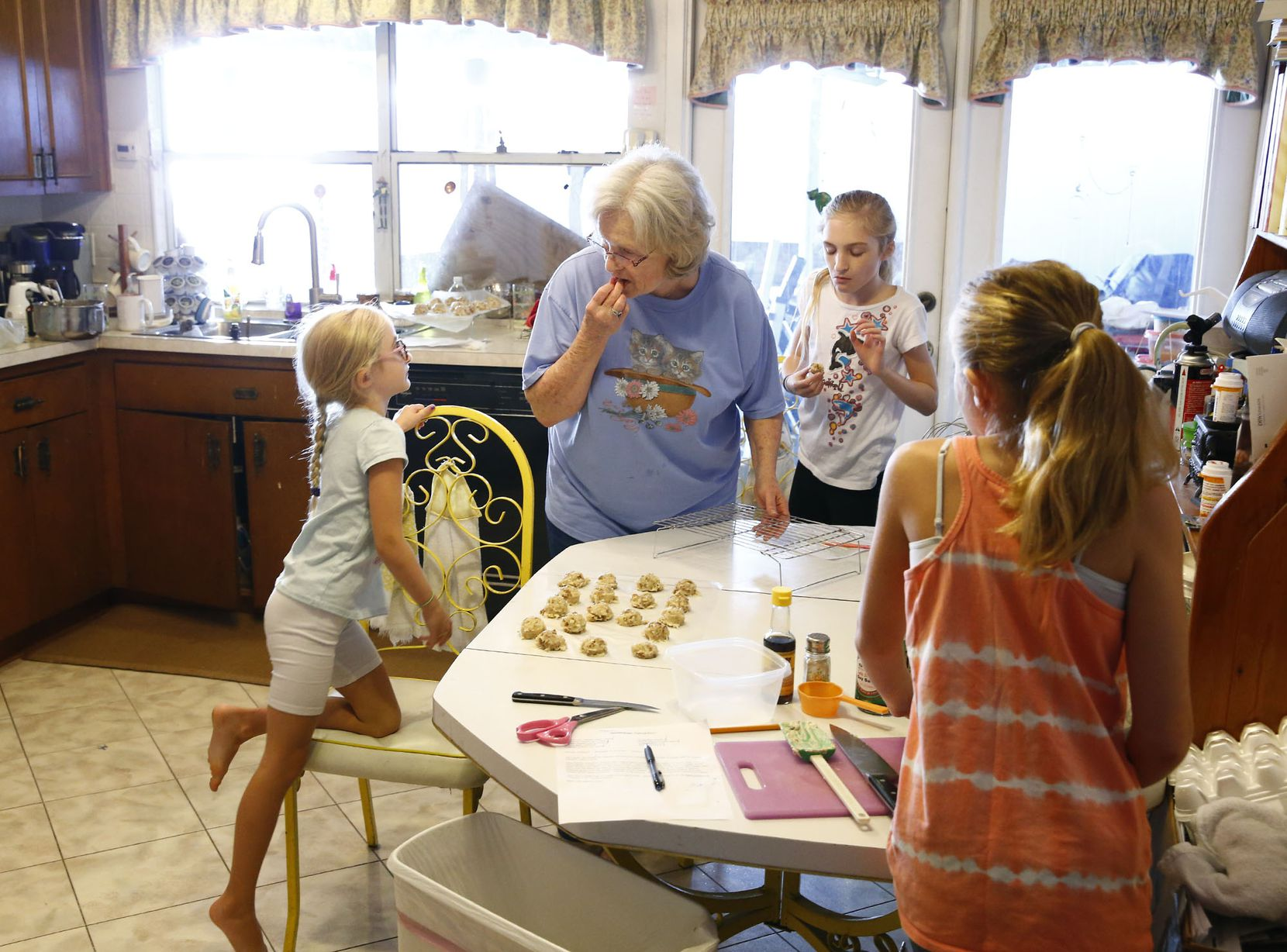 Summer Garmon, 6, (from left) looks at her grandmother Peggy Garmon with her sisters Elizabeth and Allyson, both 11, make candy at Peggy's home in Rowlett.