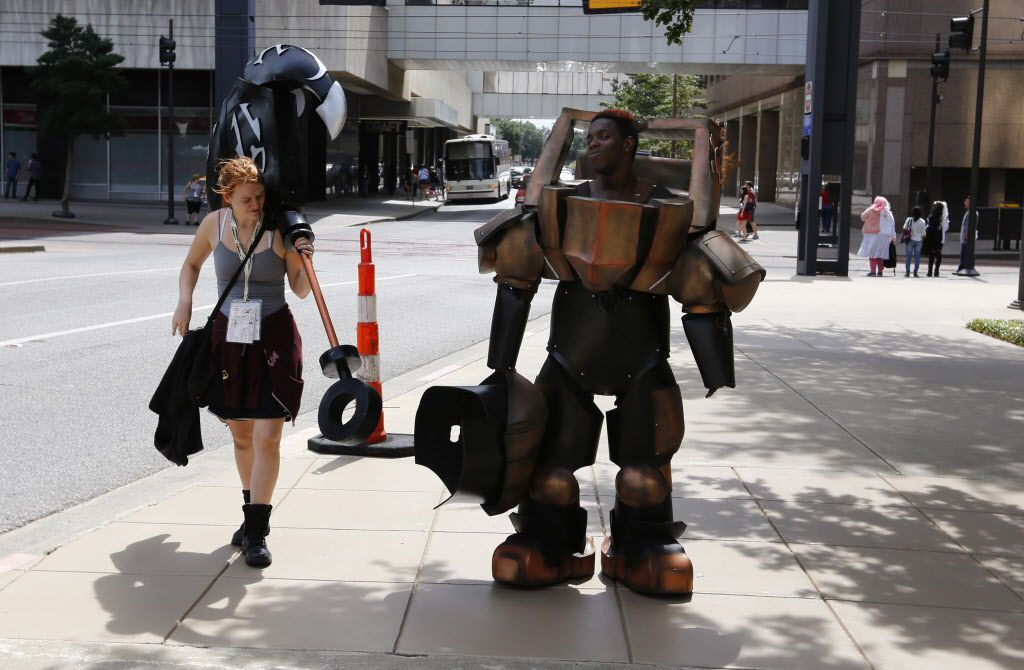 Valerie Nystrom, left, helps Hioshi Jackson, in costume as Nautilus from League of Legends walk down Olive Street as they leave AnimeFest 2015 for a costume change.