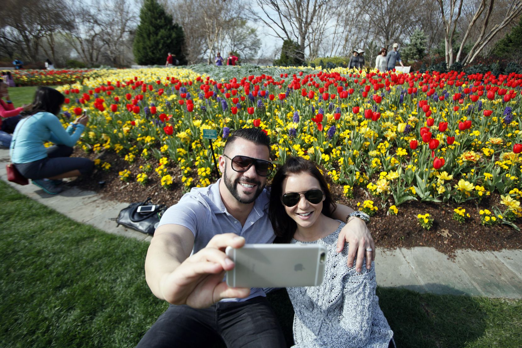 Eric Andrews and Shannon Andrews, of Lewisville, smile for a photo with a bed of tulips during the Dallas Blooms Festival at the Dallas Arboretum.