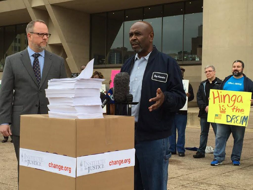 Hinga Mbogo (right) and Institute for Justice attorney Bill Maurer (left) talked in front of Dallas City Hall and behind a stack of petitions for Mbogo on Wednesday. Mbogo was fighting to keep his auto repair business on Ross Avenue more than 10 years after the city rezoned the area to prohibit auto shops like his. (Tristan Hallman/Staff)