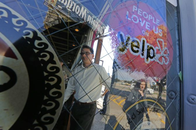Paul Hanlon and Stephenie Bowen walk into Velvet Taco, which proudly displays a Yelp sticker. The restaurant has 490 prominent reviews on the site, with a rating of four out of five stars.
