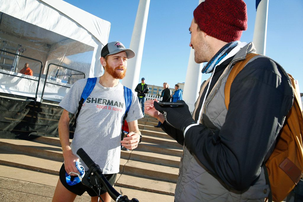 Colby Mehmen, (left) winner of the men's half marathon is greeted by Tyler Hemenway during the BMW Dallas Marathon in downtown Dallas on Dec. 10, 2017.  (Nathan Hunsinger/The Dallas Morning News)