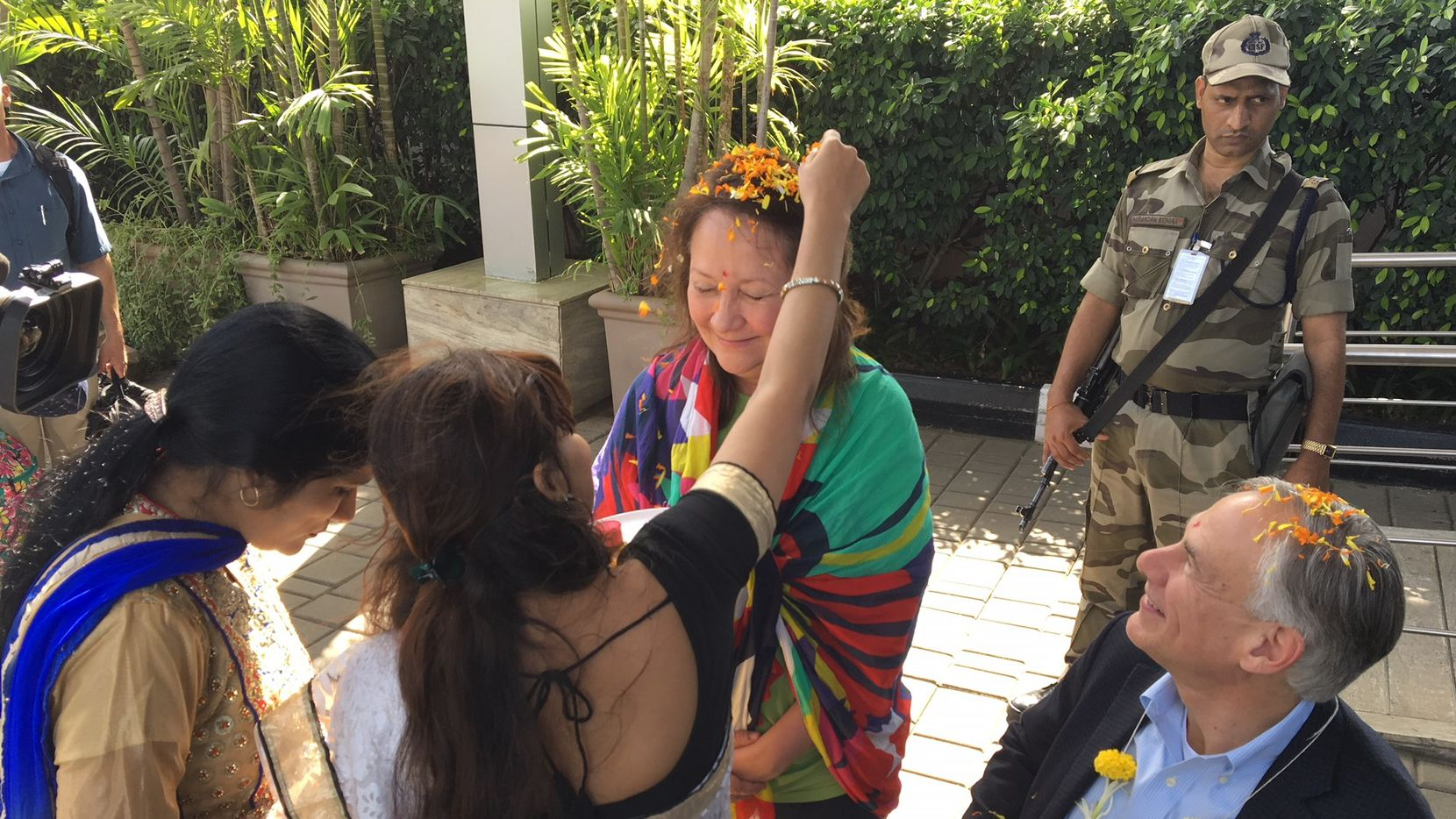 Texas Gov. Greg Abbott and first lady Cecilia Abbott each was given a colored dot, or bindi, on the forehead and draped with a garland of marigolds after arriving at Chhatrapati Shivaji International Airport on Friday.