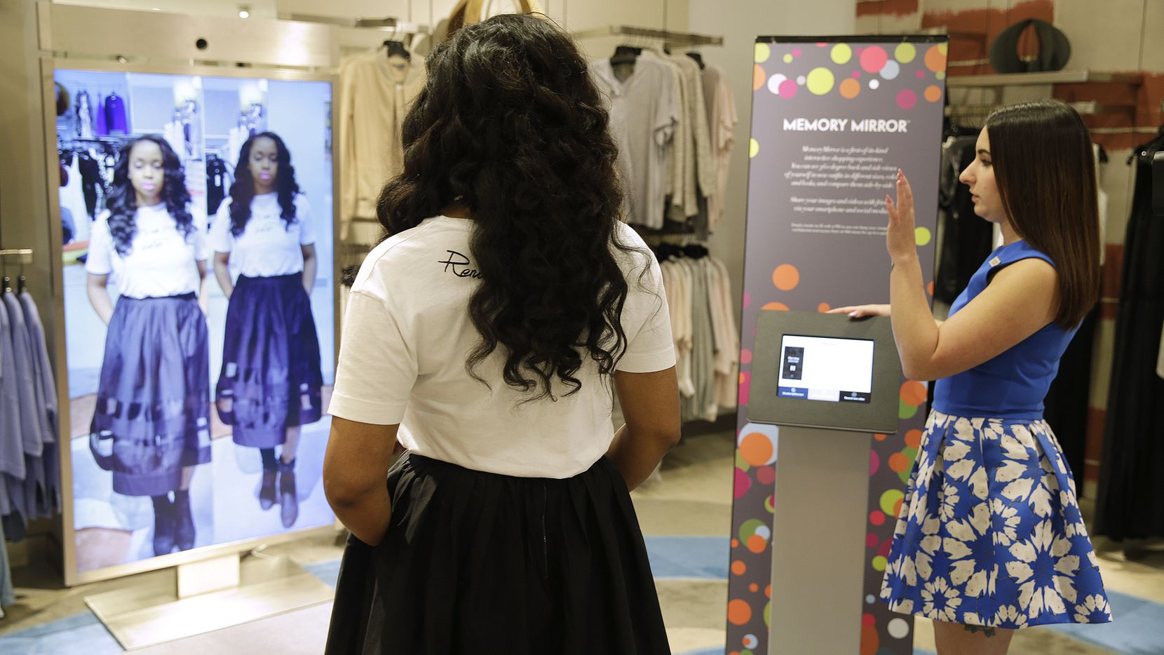 Sales manager Alysa Stefani, right, demonstrates the Memory Mirror for co-worker Porsche Colbert at the Neiman Marcus store in San Francisco's Union Square. The mirror is outfitted with sensors, setting off motion-triggered changes of clothing. The mirror also doubles as a video camera, capturing a 360-degree view of what an outfit looks like and making side-by-side comparisons.
