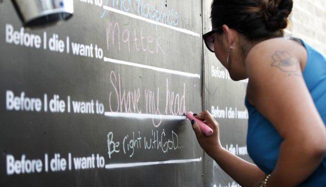 Sonia M. Farina escribe 'rasurarme la cabeza'' en el tablero de deseos ''Before I die' (Antes de morir) enfrente de 'la tienda Trader Joe's en la Greenville Avenue de Dallas. (DMN/KYE R. LEE)