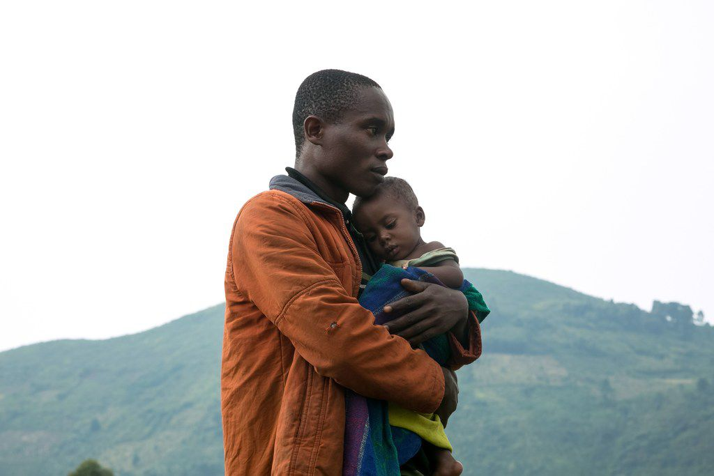 A Congolese man holds his child after he crossed the border from the Democratic Republic of Congo to be refugees at Nteko village in western Uganda.