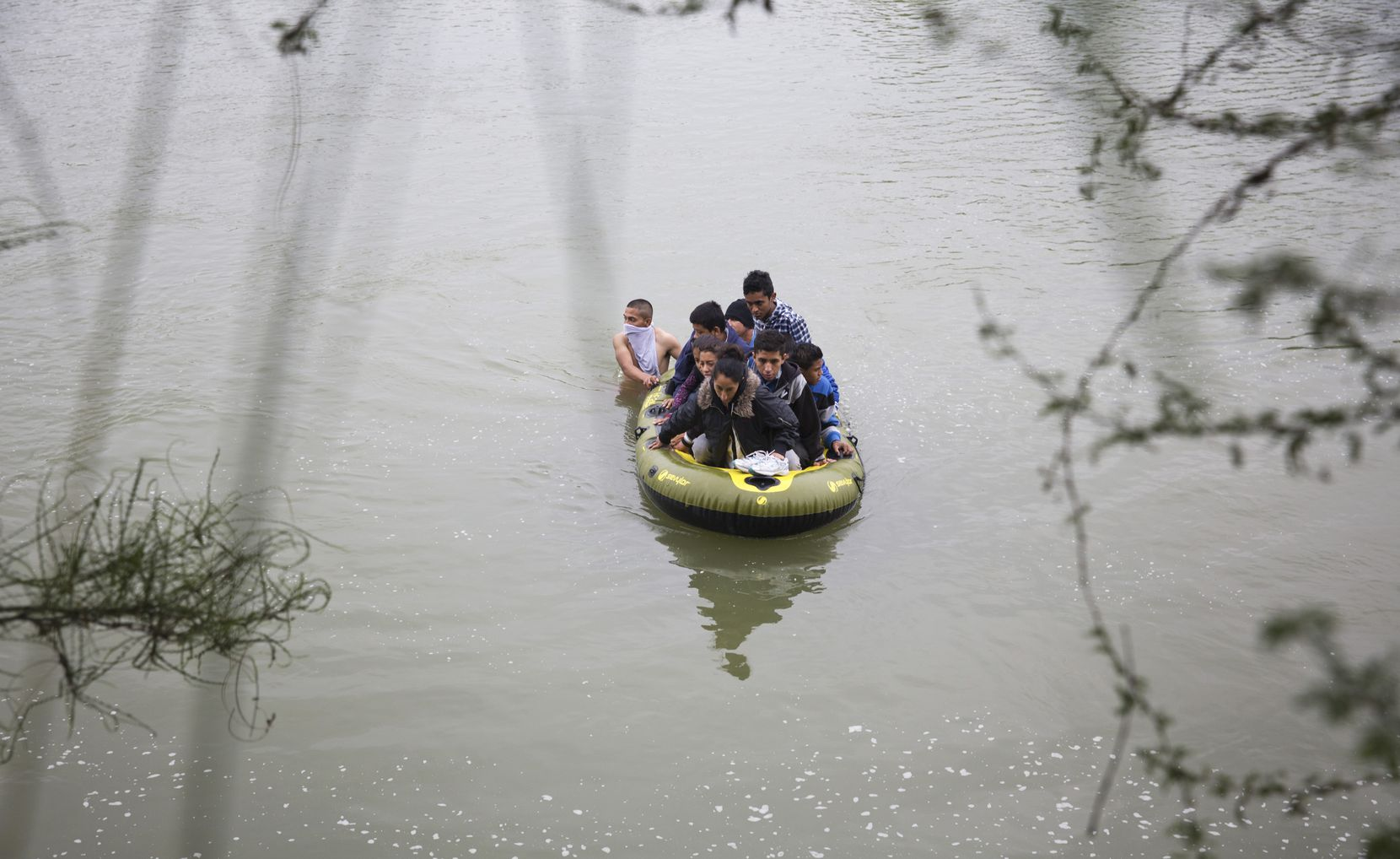 Two guides lead a raft full of migrants from Honduras and Guatemala across the Rio Grande in full view of the U.S. Border Patrol, at the border between Mexico and the U.S.