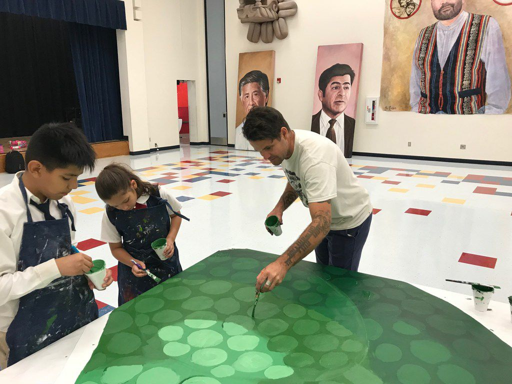 Artist Roger Peet works with students Alan Diaz and Azalae Custodio on Wednesday, August 22 at La Fe Culture and Technology Center in El Paso as they put the finishing touches on a mural to highlight endangered animals and plants threatened by any future border wall.