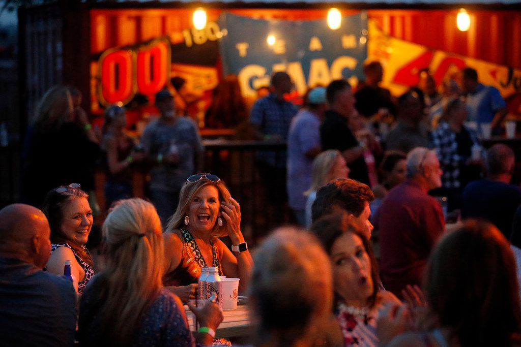 People gathered on picnic tables to watch Fleetwood Mac and Eagles tribute bands perform during opening night at ChopShop Live in Roanoke, Texas, Friday, July 6, 2018. (Tom Fox/The Dallas Morning News)
