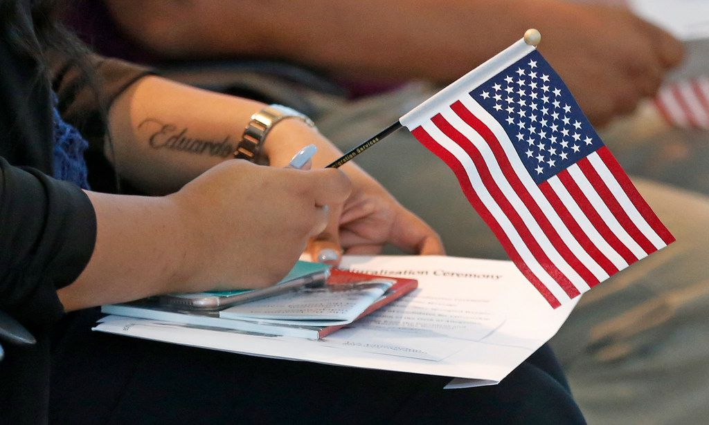 A citizenship candidate holds an American flag as she awaits the start of a naturalization ceremony at the U.S. Customs and Immigration Services regional headquarters in Irving in August.