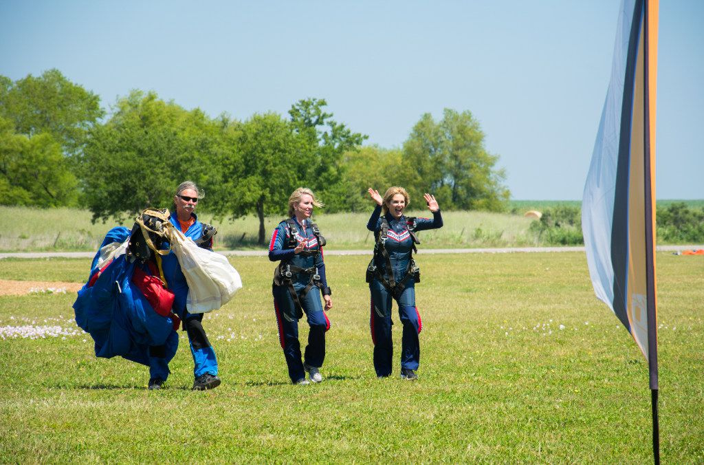 Amy Turner (middle) and Tanya Foster (right, waving) celebrate after parachuting to raise funds for the Birds Eye View Project.