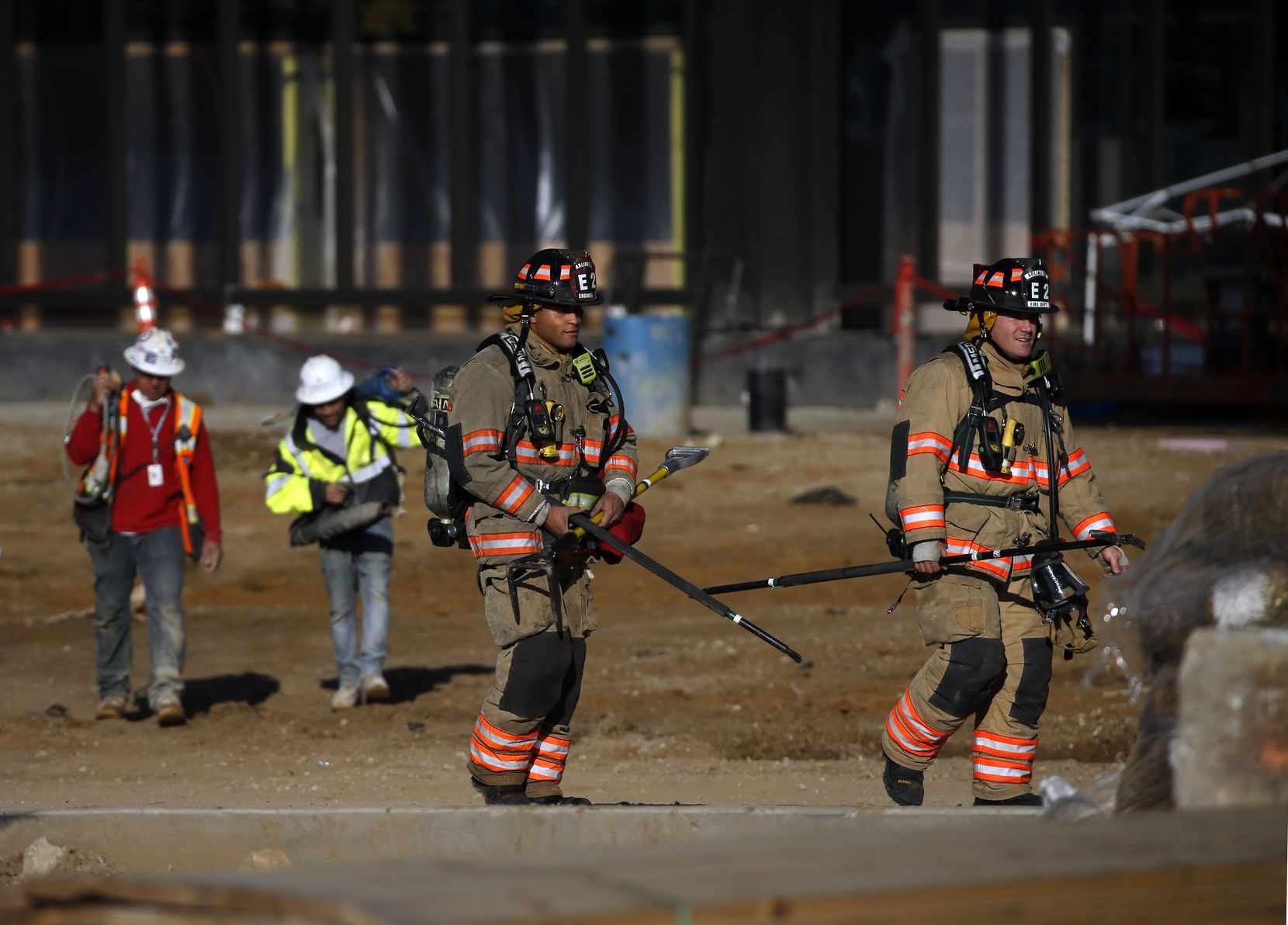 Arlington firefighters and construction workers leave the scene of a fire in the upper concourse of the Globe Field Field under construction in Arlington, Texas, Saturday, December 14, 2019.