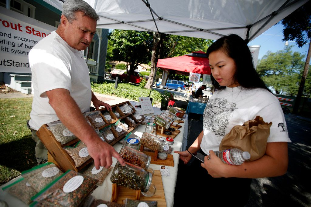 Rick Stricklin, left, of the Sprout Stand, talks to Catherine Nguyen at the McKinney Farmers Market.