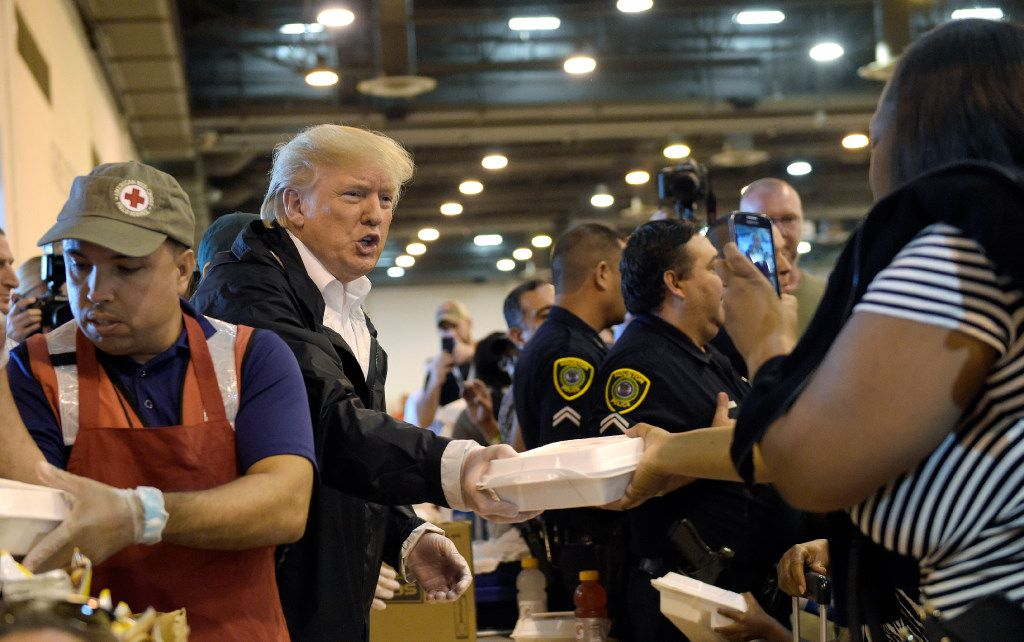 President Donald Trump passes out food and meets people impacted by Hurricane Harvey during a visit to Houston's NRG Center Saturday. It was his second trip to Texas in a week.
