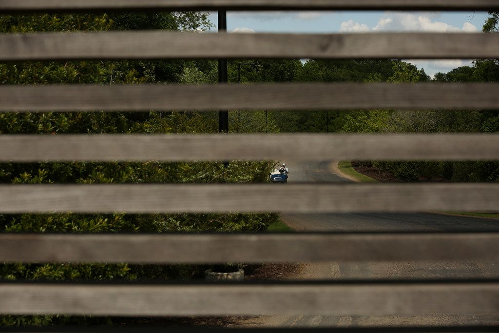 Seen through the gate at the entrance, golf carts are used to shuttle guests from the parking lot before Dallas Mayor Mike Rawlings speaks at the 2018 GrowSouth Annual Report event at the Trinity Forest Golf Club in Dallas on Thursday, May 24.