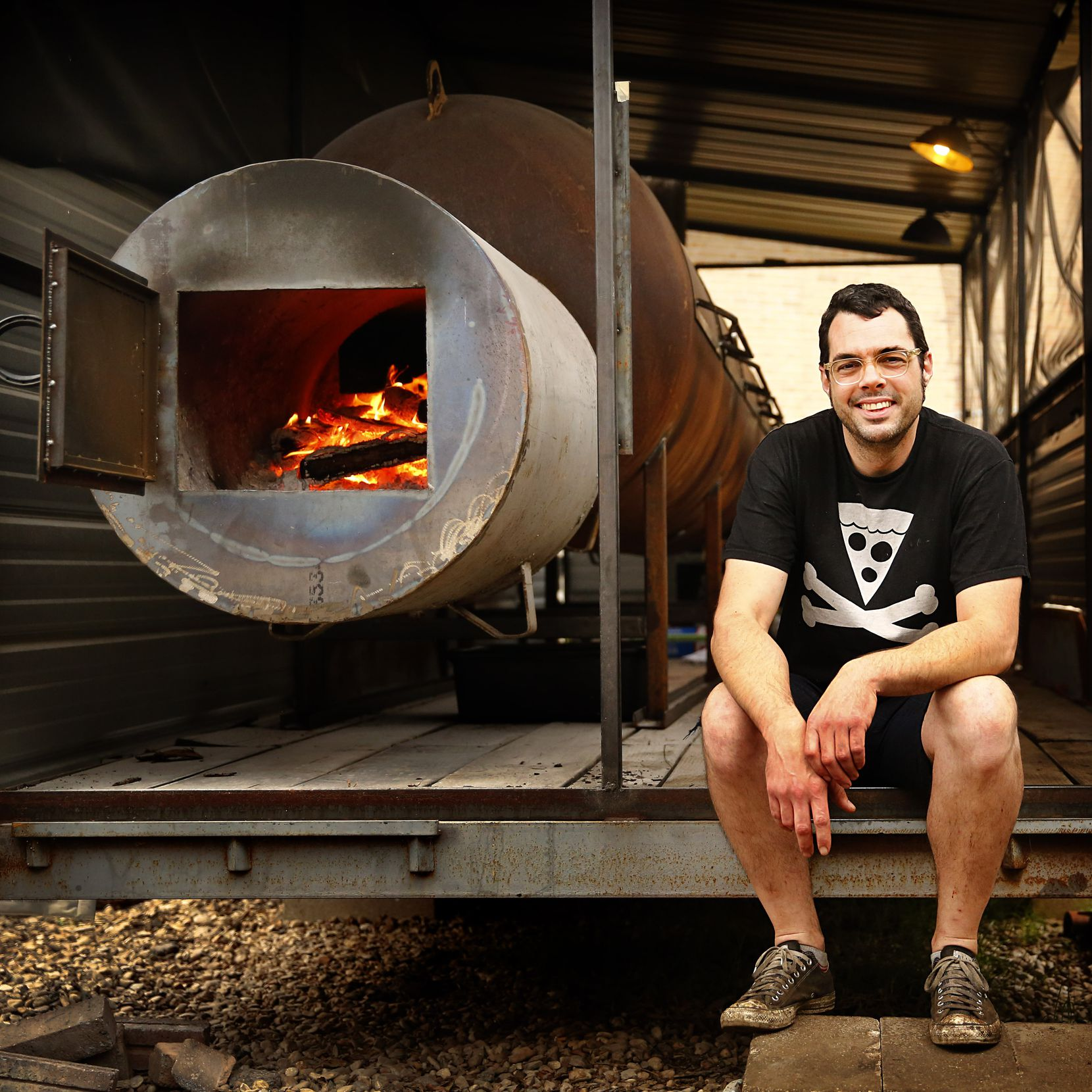 Famed pitmaster Aaron Franklin poses with his smoker behind Franklin Barbecue in 2013 on Day 2 of the Texas BBQ Posse's Best of Texas BBQ Tour.