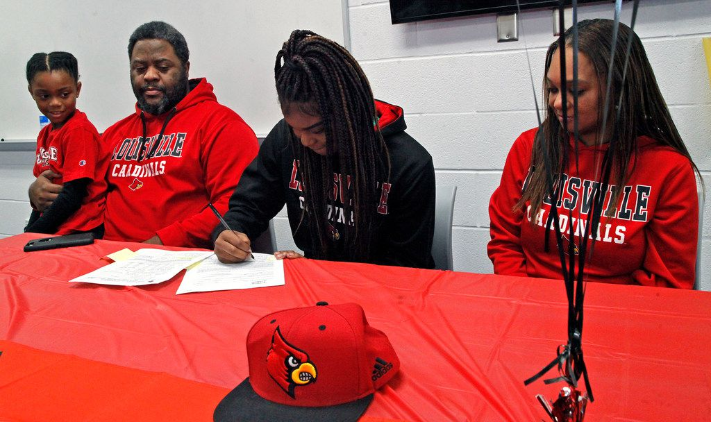 Allen High School student Nyah Green signed her letter of intent to play basketball for Louisville on Wednesday morning, November 14, 2018.  Looking on are her sister Keira (left), 9, father Quinton and mother Latrice (right) at Allen High School. (Stewart F. House/Special Contributor)