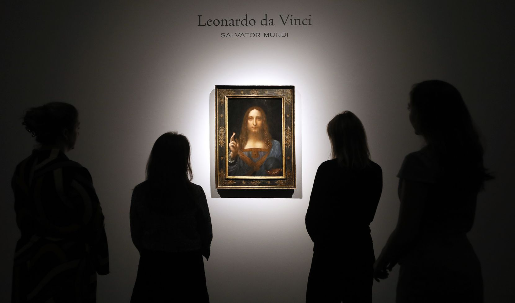 "People gathered around Leonardo da Vinci's ""Salvator Mundi"" at a Christie's auction room in London in October 2017."
